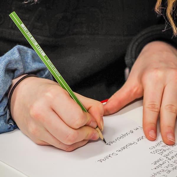 Oppilas kirjoittaa kynällä paperille.