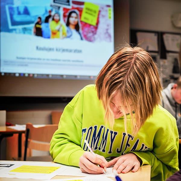 Oppilas tekemässä tehtäviä luokkahuoneessa.