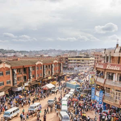 Kuva Ugandasta, kadulla on paljon ihmisiä ja autoja.