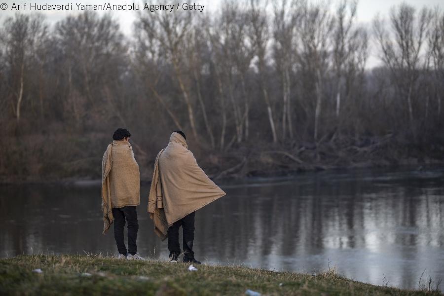 Kaksi siirtolaista Evros-joen rantapenkereillä