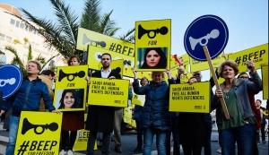 Ihmisiä kylttien kanssa, joissa vaaditaan vapauttamaan kaikki ihmisoikeuspuolustajat.
