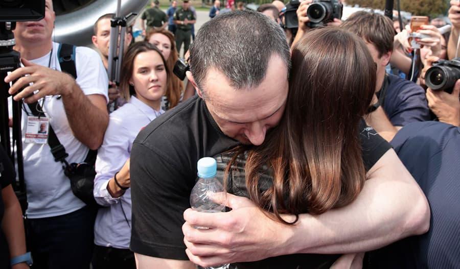 Kuvassa Oleg Sentsov halaa henkilöä median edustajien ympäröimänä.