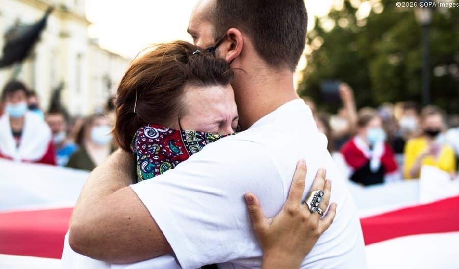Kaksi ihmistä halaa Valko-Venäjällä mielenosoituksessa