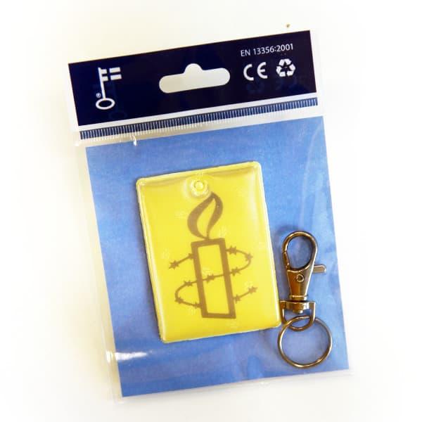 Kuvassa pakkauksessa oleva keltainen heijastin, jossa Amnestyn musta kynttilälogo.