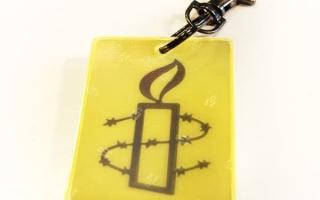 Kuvassa keltainen heijastin, jossa Amnestyn musta kynttilälogo.