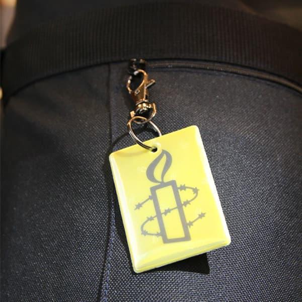 Kuvassa vaatteeseen kiinnitetty keltainen heijastin