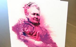 Valkoinen kortti, jonka kannessa violetti-vaaleanpunainenhko Minna Canth