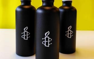 Kolme mustaa juomapulloa, Amnestyn logo valkoisella