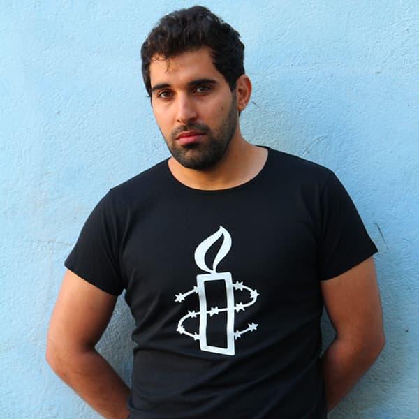 Mies pitää mustaa paitaa, jossa valkoinen Amnestyn logo